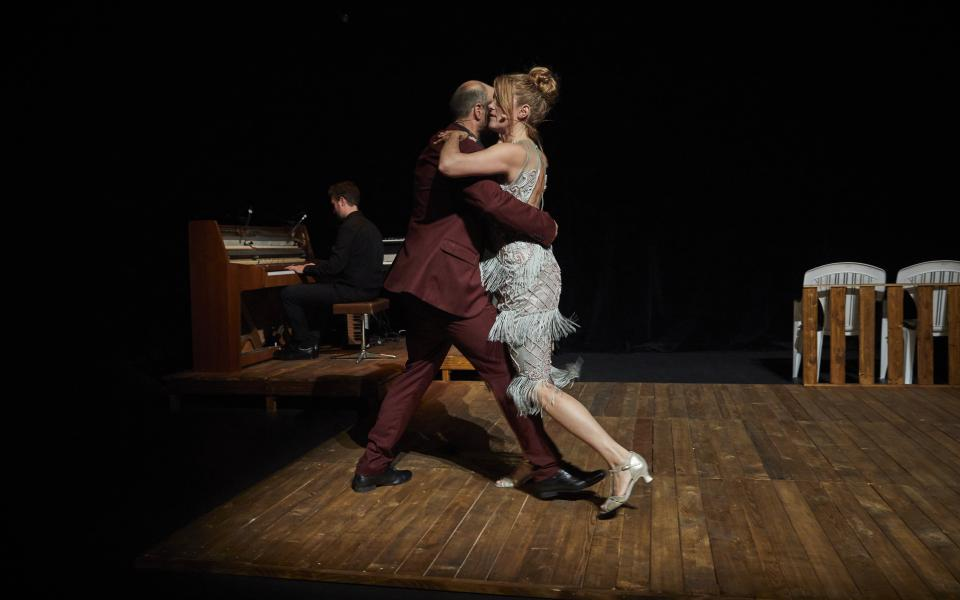 A man and a woman dancing in a semi-dark waltz, on a brown wooden floor